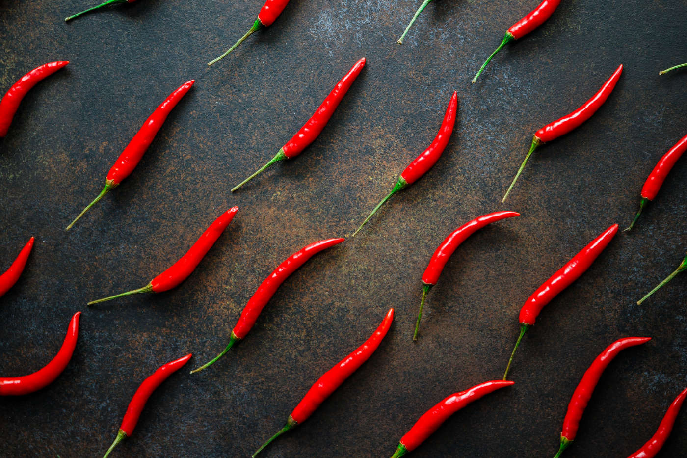 a-lot-of-chili-peppers-on-a-kitchen-table-top-view-MC2X8WH.jpg